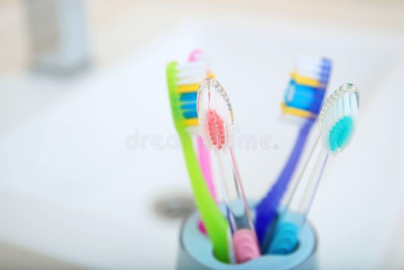 用不同的牙刷的杯临近水槽,特写镜头 库存照片