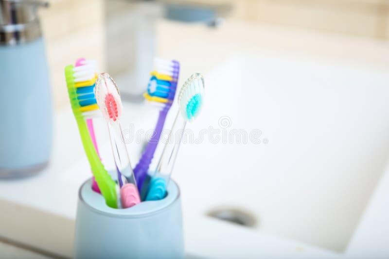 用不同的牙刷的杯临近水槽 免版税库存图片