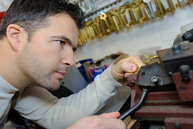 用不同的类型钥匙的年轻专家在锁匠 免版税库存照片