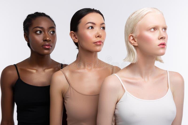 用不同的肤色佩带的女用短袖衬衣的三名妇女 免版税图库摄影