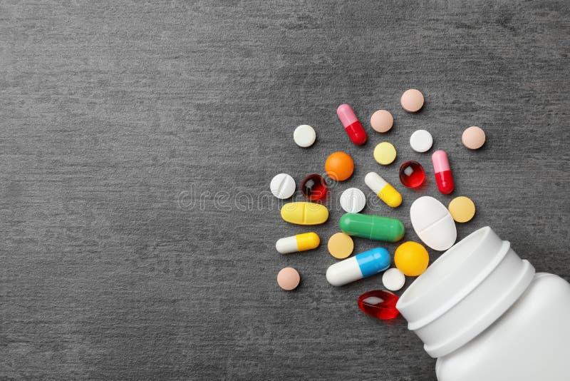 用不同的药片的瓶在灰色背景,平的位置 免版税库存照片
