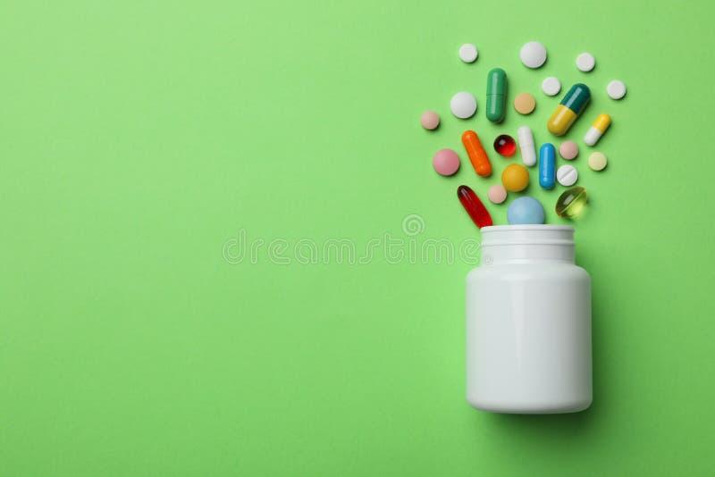 用不同的药片的瓶在颜色背景,平的位置 免版税库存图片