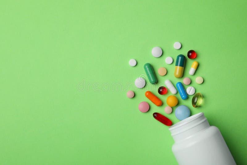 用不同的药片的瓶在颜色背景,平的位置 库存图片