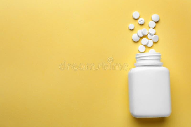 用不同的药片的瓶在颜色背景,平的位置 免版税库存照片