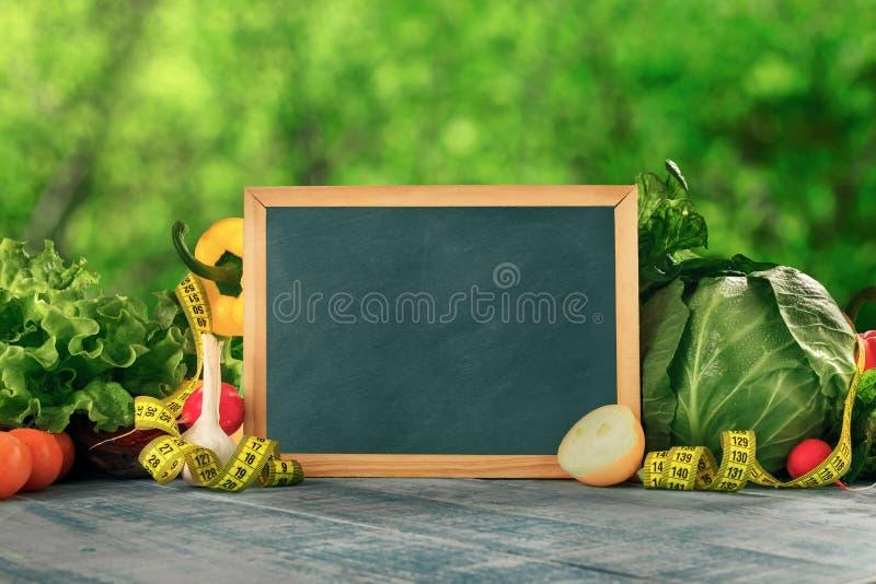 用不同的菜和测量的t的小空的黑板 库存照片