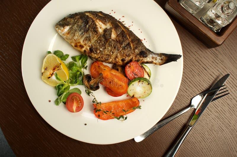 用不同的菜的被烘烤的鱼是基本的健康食品 免版税库存图片