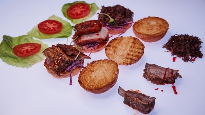 用不同的装填的三个开放汉堡用被撕毁的猪肉,与肋骨和猪排在一张白色桌上 库存照片