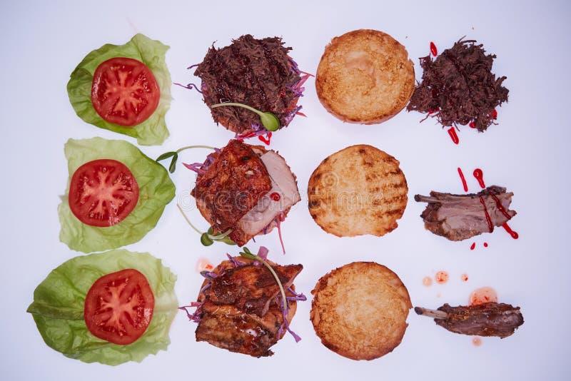 用不同的装填的三个开放汉堡用被撕毁的猪肉,与肋骨和猪排在一张白色桌上 免版税库存图片