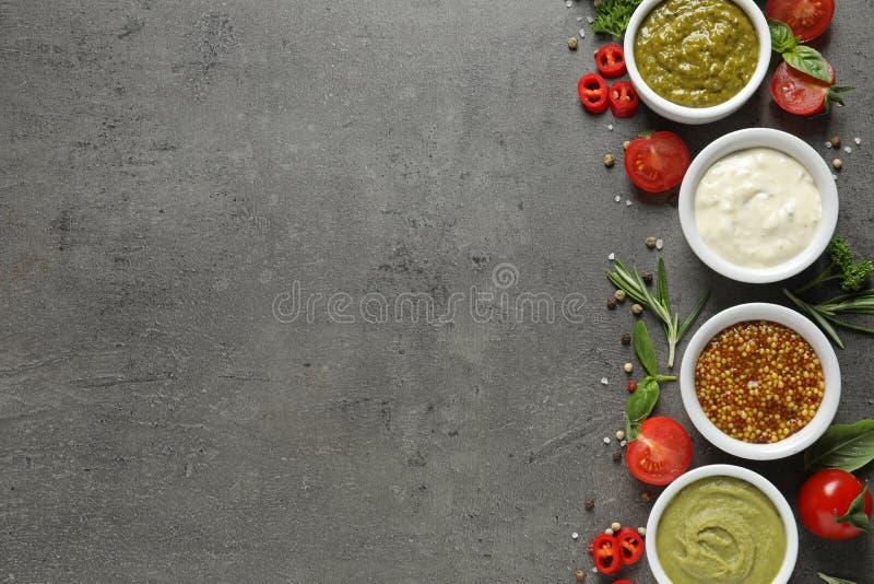 用不同的调味汁和成份的碗在灰色背景,平的位置 免版税图库摄影