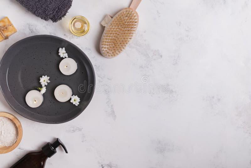 用不同的身体和皮肤护理精华的温泉有浮动蜡烛的静物画和碗 库存照片
