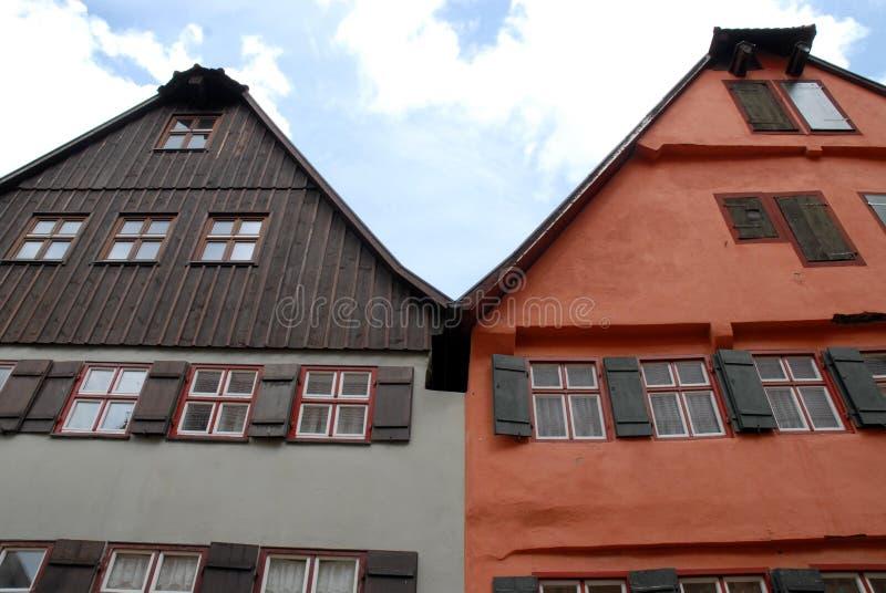 用不同的颜色的两个与白色窗口的房子和窗口在Dinkelsbuhl镇在德国 免版税库存照片