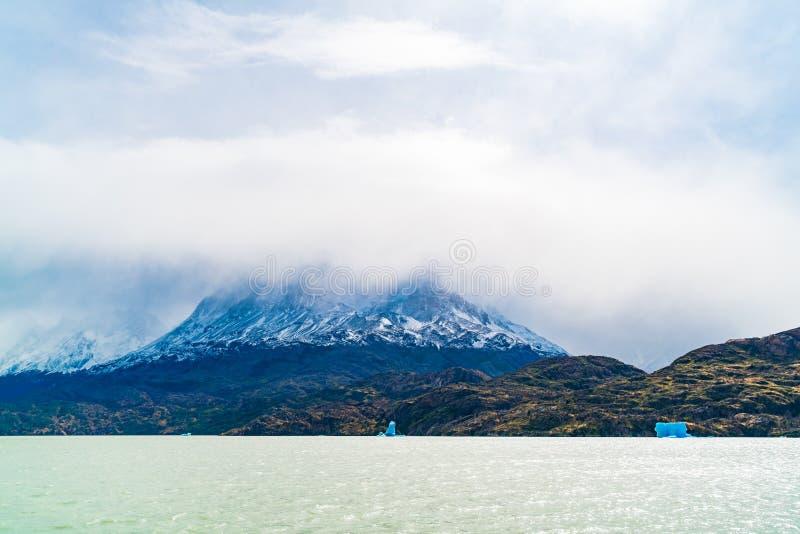 用与冰山的雾盖的美丽的雪山看法终止灰色冰川和漂浮在灰色湖 免版税库存图片