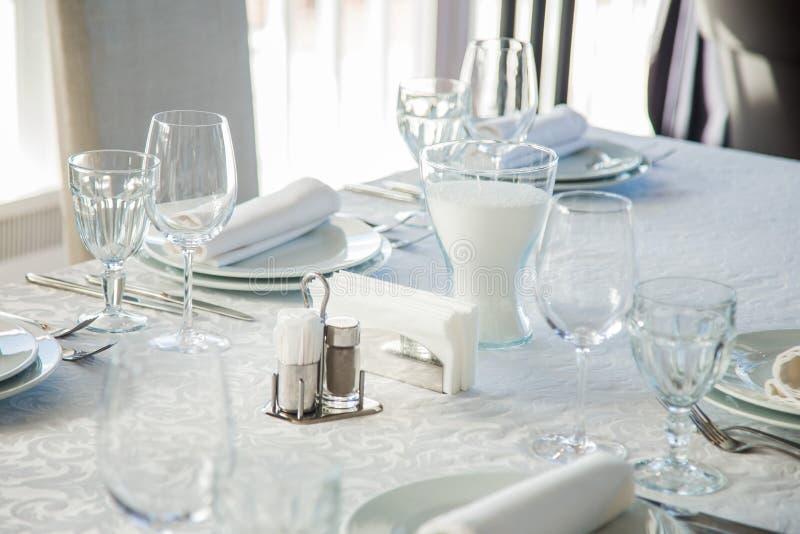 用与利器和玻璃的一张白色桌布盖的一张长的桌 图库摄影