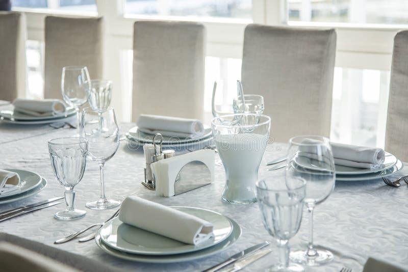 用与利器和玻璃的一张白色桌布盖的一张长的桌 库存图片