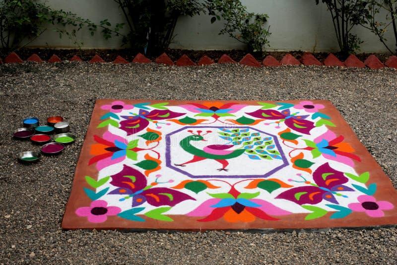 用与孔雀、花和蝴蝶的干燥搽粉的颜色做的五颜六色的Rangoli传统花卉设计 免版税库存照片