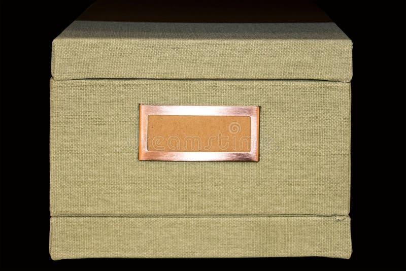 用与空白的标签的花呢织品盖的减速火箭的轻的卡其色的文件存贮箱子在铜框架 免版税库存图片