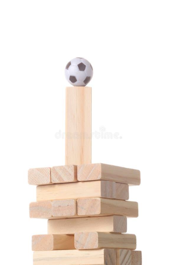 用与脚球的木块做的塔在被隔绝的上面在与裁减路线的白色背景和您的拷贝空间 库存照片
