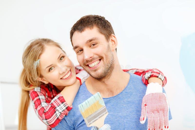 用与画笔的油漆报道的微笑的夫妇 免版税库存图片