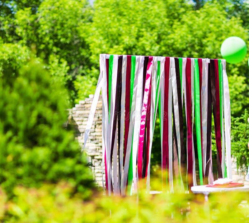 用丝带装饰的优美地雅致婚姻曲拱,夏天 免版税库存照片