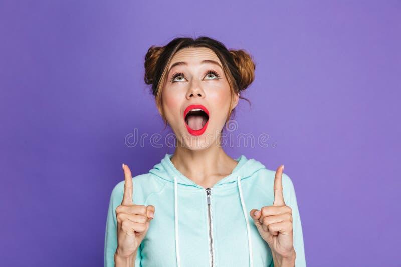 用两个小圆面包指向手指的快乐的深色的女孩画象  免版税库存照片
