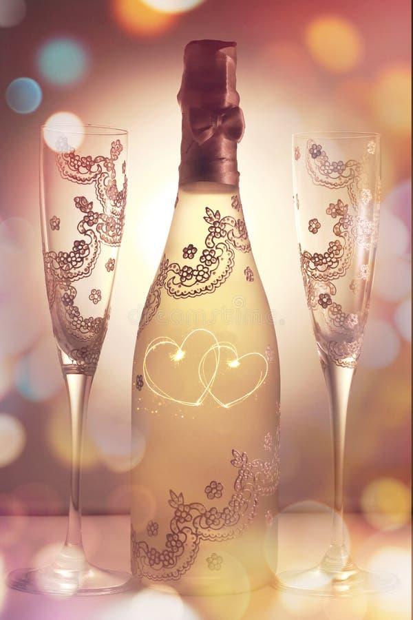用两香槟和两glases装饰的瓶交错心脏 免版税库存图片