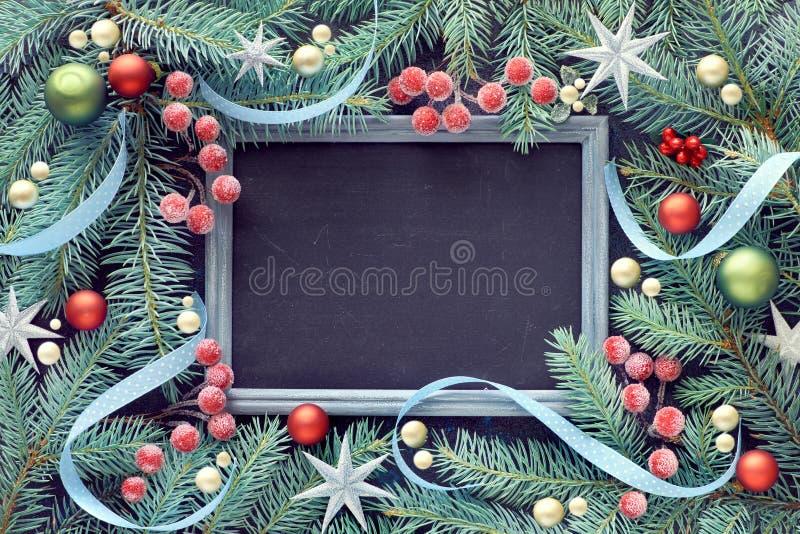 用中看不中用的物品、莓果和星装饰的冷杉枝杈,黑板, 免版税库存照片