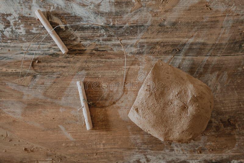 用串切开的黏土片断说谎在为瓦器轮子准备的木桌上 免版税库存照片