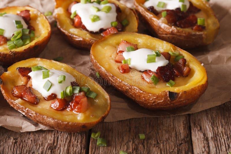 用乳酪、烟肉和酸性稀奶油特写镜头充塞的土豆 贺尔 库存照片