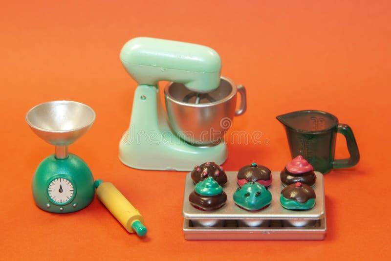 用于制作面团、测量杯、滚针、鳞片和橙色背景上的成品蛋糕的烹饪机 库存图片
