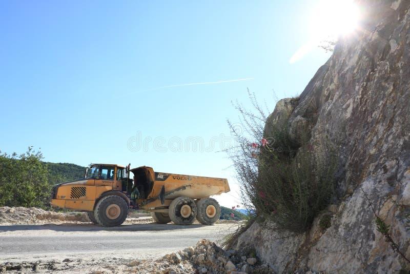 用于卡拉拉大理石猎物的倾销者卡车 大黄色dum 库存照片
