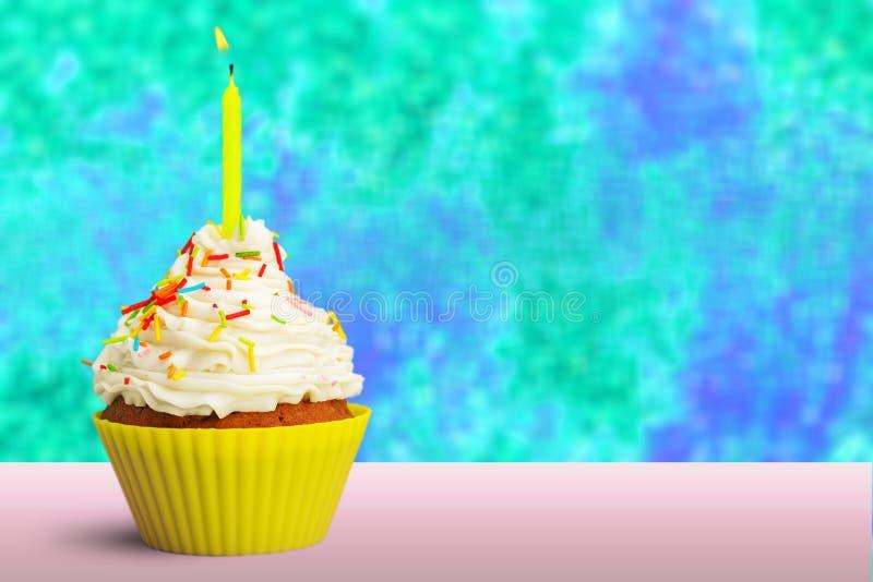 用五颜六色的生日蜡烛装饰的杯形蛋糕 免版税库存图片