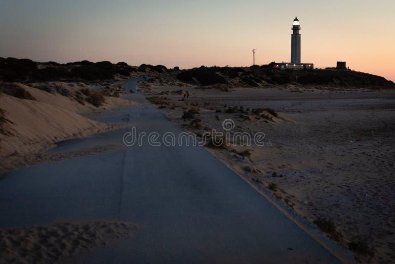 用从沙丘路的沙子盖的路往特拉法加,卡迪士,日落的西班牙灯塔  库存图片