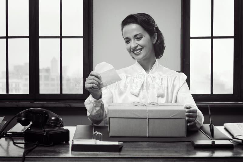 用信件接受礼物盒的微笑的妇女 免版税库存照片