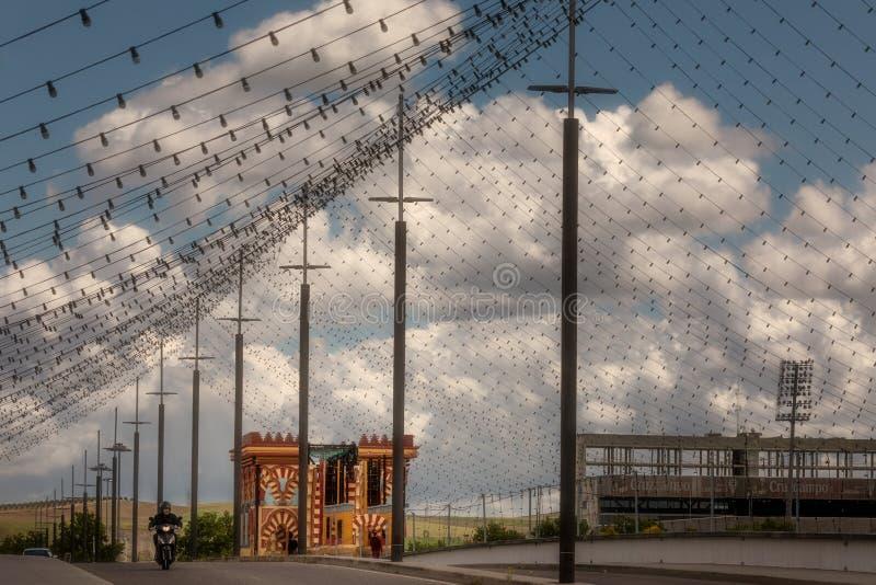 用公平的电灯泡装饰的阿雷纳尔桥梁在多云天空下 免版税库存照片
