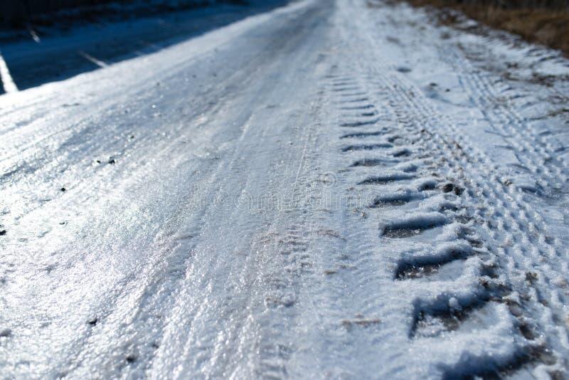 用冰盖的路,汽车轨道 免版税库存照片