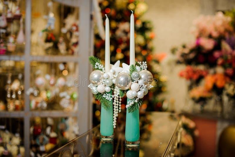 用冷杉分支、小珠和小的玻璃球装饰的两个装饰圣诞节蜡烛 图库摄影