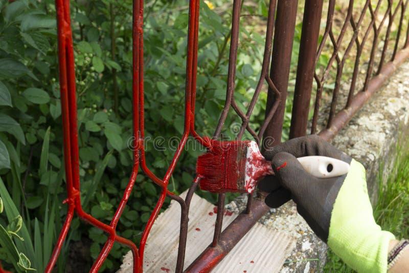 用刷子画金属栏杆构造的手 库存照片