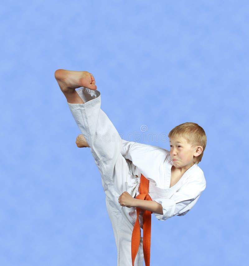 用功运动员训练在轻的背景的反撞力yoko-geri 免版税库存照片