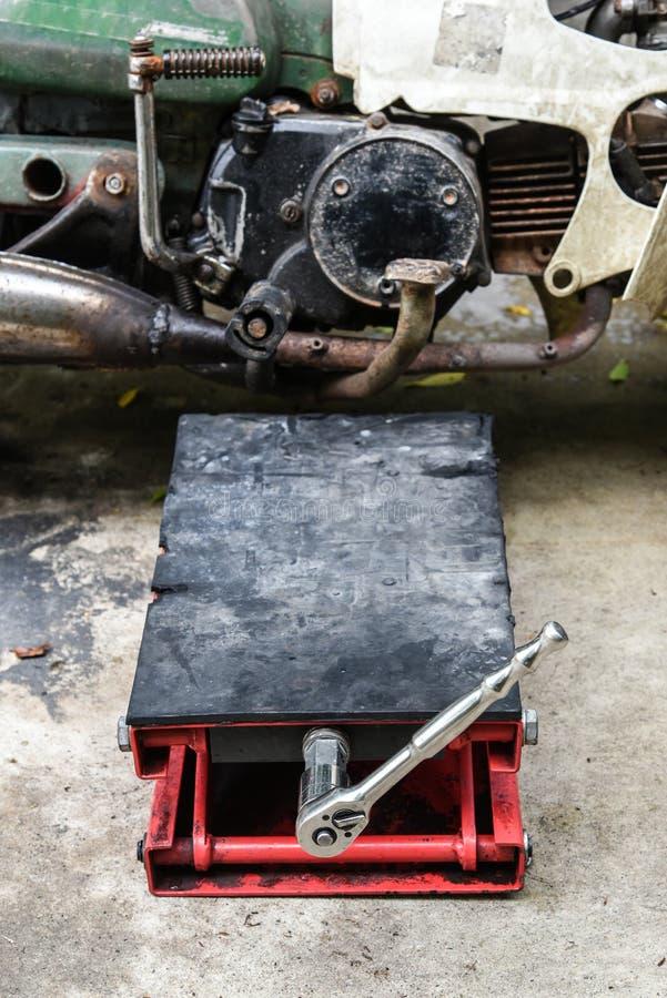 用千斤顶压出或拔出器拔出准备好对老摩托车修理公司,用千斤顶压出或拔出器拔出为 免版税库存照片