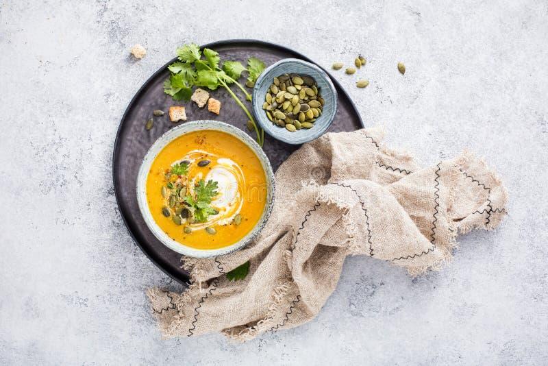 用南瓜籽和新鲜的香菜叶子装饰的一个碗南瓜汤芬芳自创奶油 图库摄影