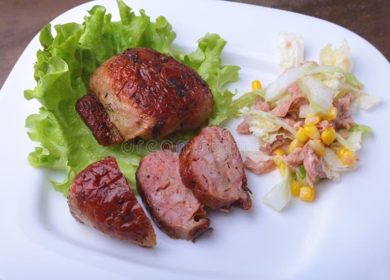 用卤汁泡的roaste鸡胸脯在BBQ烹调了并且服务用在白色板材,特写镜头的新鲜的沙拉 库存图片