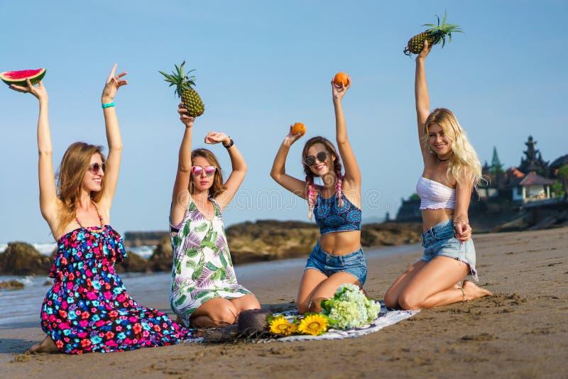 用各种各样的果子花费时间的小组美丽的年轻女人 图库摄影