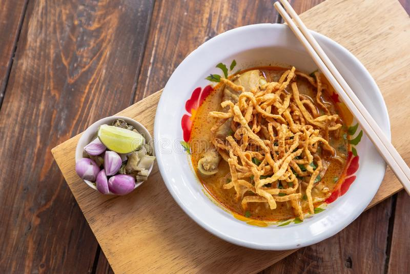 用咖喱粉烹调的汤面Khao soi用鸡肉和辣椰奶在木桌上 免版税库存照片