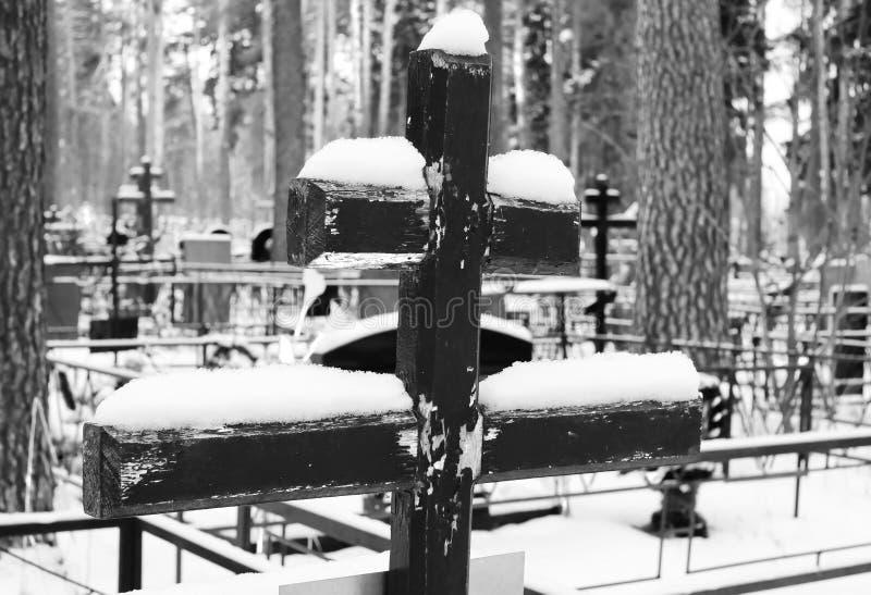 用在一座正统公墓的坟墓的雪报道的一个老木十字架的黑白图象在冬天 库存图片