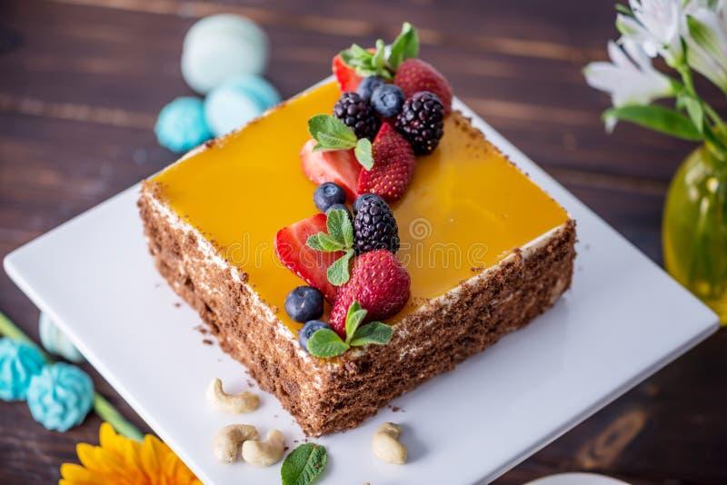 用在上面和莓果的黄色果冻装饰的自创方形的蛋糕用在黑暗的背景的薄菏 免版税图库摄影