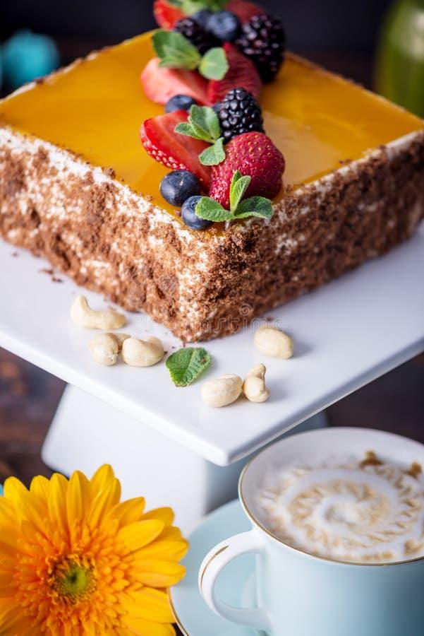 用在上面和莓果的黄色果冻装饰的自创方形的蛋糕用在黑暗的背景的薄菏 库存图片