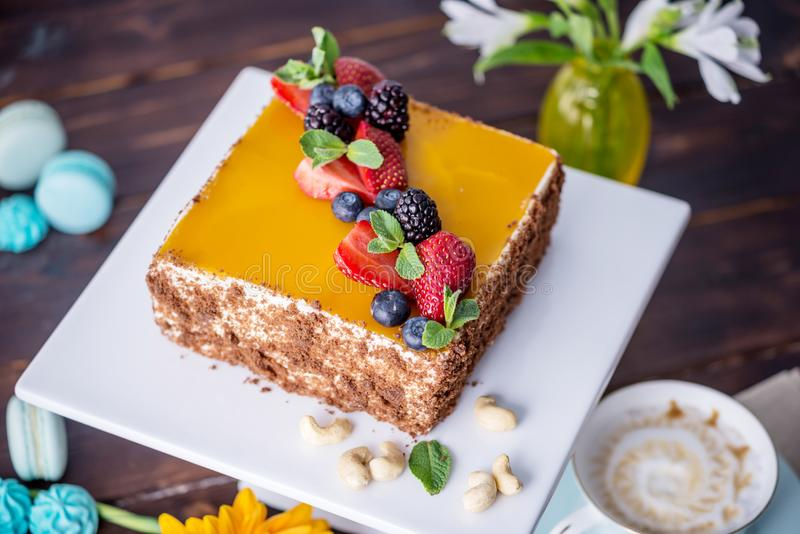 用在上面和莓果的黄色果冻装饰的自创方形的蛋糕用在黑暗的背景的薄菏 库存照片