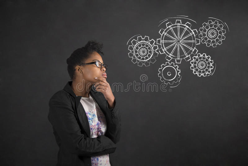 用在下巴的手认为与在黑板背景的齿轮的非洲妇女 库存照片