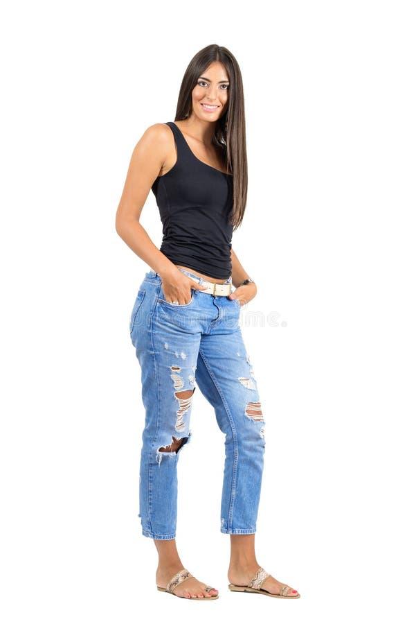 用在口袋的手微笑对照相机的年轻愉快的被晒黑的妇女 免版税库存图片