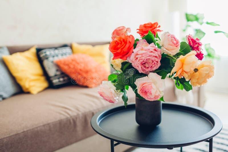 用在咖啡桌和舒适长沙发上的花装饰的客厅内部有坐垫的 新鲜的玫瑰 库存图片